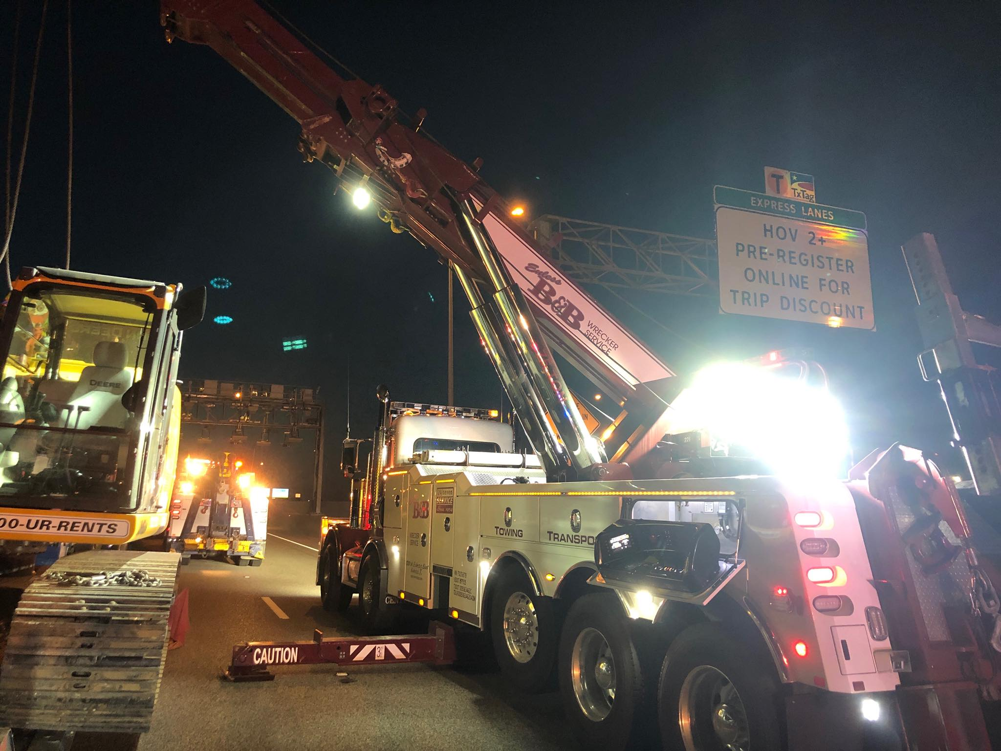 Euless B&B Wrecker Service using a crane to for heavy equipment towing after an 18-wheeler carrying a John Deer hit a wall and blew a front tire.